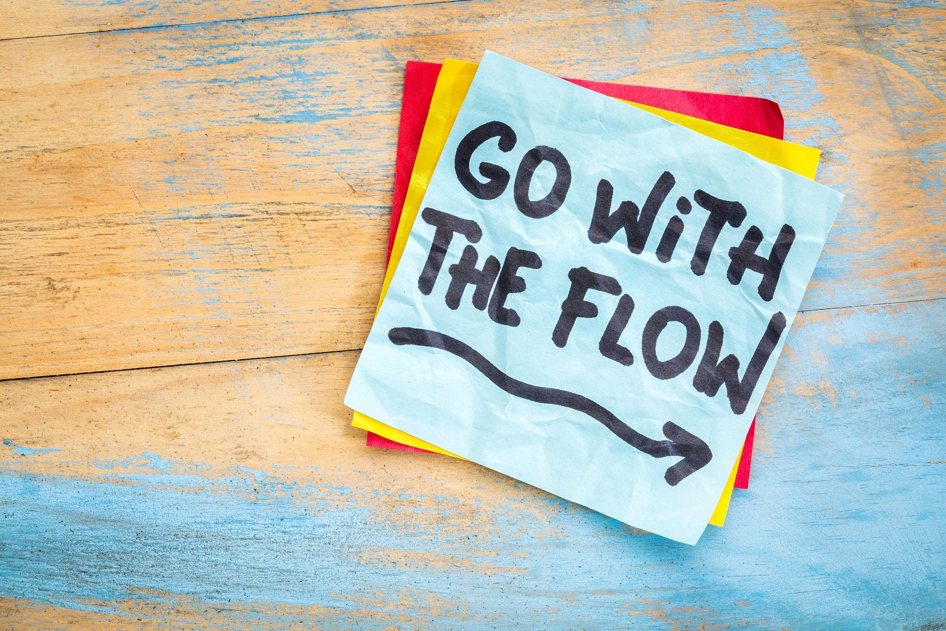 50156097 - go with the flow advice or reminder on a sticky note against grunge painted wood